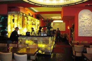 Im Bar- und Eingangsbereich reichen sich Gold- und Holzelemente die Hand.